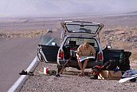 A man sitting on tailgate of car in the desert near Lone Pine CA