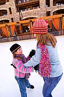 A mother and daughter dancing together on ice skates at Northstar ski resort near Lake Tahoe in California