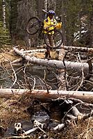 A man carrying his mountain bike across a stream while mountain biking near Truckee CA