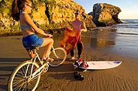 A woman on a cruiser bike and a man with a surfboard on the beach at Natural Bridges State Park in Santa Cruz in California