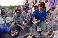 A caucasian woman making chapati bread with some Balti men in Pakistan