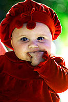 baby in red outfit sucking fingers
