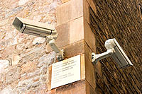 Surveillance cameras and sign in Catalan, Spanish and English warning of cameras presence