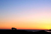 Silhouette of car on mountain ridge at sunset overlooking the ocean