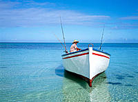 Trou-Aux-Biches beach, fisherman leaving on his boat in early morning. Mauritius Island