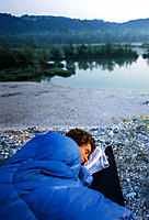 Morning dawn over young woman in sleeping bag at the shore of the reservoir lake of the Isar river near Icking, Upper Bavaria, Germany