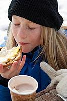 Young girl eating a sandwich and drinking hot chocolate outdoors in the winter