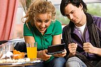 Teenage boy and girl with handheld game