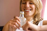 Teenage girl with bottle of spirits