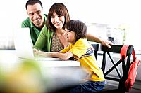 Parents Watching Son Use Laptop at Home