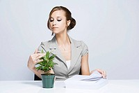 Businesswoman Looking at Plant