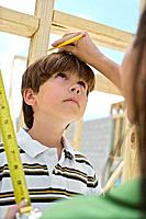 Mother Measuring Little Boy in Unfinished House