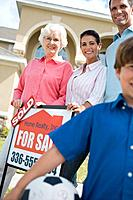 Family Standing with Sold Sign for House (thumbnail)