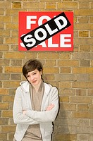 Young woman and sold sign