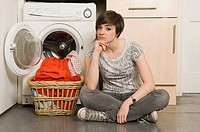 Young woman by washing machine