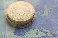 Pound coins on euro note