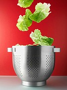 Salad leaves falling into colander