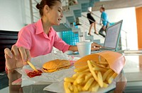 Businesswoman eating French fries, working on laptop