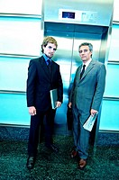 Businessmen waiting for elevator, portrait