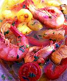 Gambas with oil, herbs, tomatoes, onions and garlic