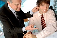 Businessman holding ear of colleague in office