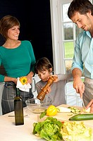 Mid adult man and a young woman preparing food with their son