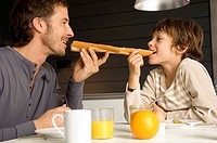 Mid adult man eating a baguette with his son (thumbnail)
