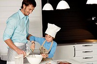 Mid adult man making a cake with his son in the kitchen (thumbnail)