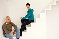 Portrait of a mature man and a mid adult woman sitting on a staircase