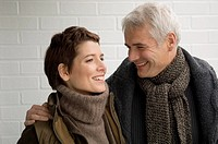 Close_up of a mature man arm around a mid adult woman and smiling