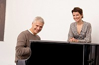Portrait of a mature man playing a piano and a mid adult woman standing near him