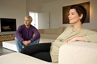 Mature man and a mid adult woman sitting in a living room