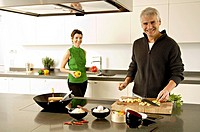 Portrait of a mature man and a mid adult woman preparing food in the kitchen