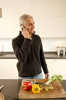 Mature man talking on a mobile phone in the kitchen