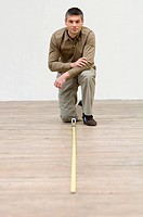 Interior designer measuring the hardwood floor with a tape measure