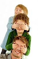 Girl covering eyes of her father and her eyes covered by her brother