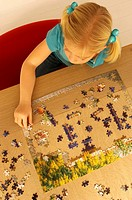 High angle view of a girl playing a jigsaw puzzle (thumbnail)
