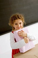 Portrait of a girl holding a gift and smiling