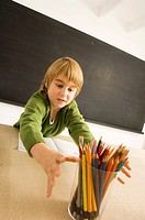 Boy reaching out for a pencil holder