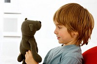 Side profile of a boy holding a teddy bear