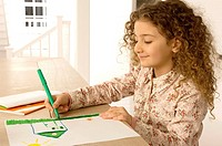 Close_up of a girl coloring on a sheet of paper