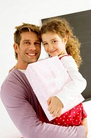 Portrait of a mid adult man carrying his daughter with a gift