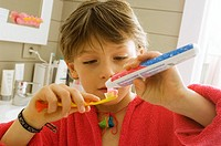 Close_up of a boy holding a toothpaste and a toothbrush