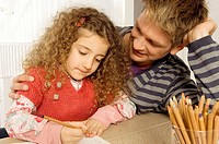 Girl drawing with her father sitting beside her