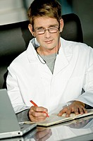 Portrait of a male doctor sitting at a desk in his office and writing in a notebook