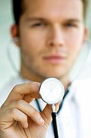 Close_up of a male doctor holding a stethoscope