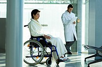 Female patient sitting in a wheelchair and a male doctor standing in the background