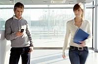 Businesswoman walking beside a businessman at an airport (thumbnail)