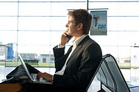Side profile of a businessman using a laptop and talking on a mobile phone at an airport lounge