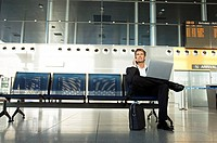 Businessman using a laptop and talking on a mobile phone (thumbnail)